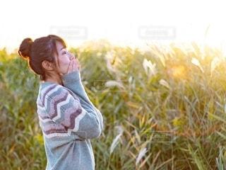 ススキ草原で立っているセーターを着た女性の写真・画像素材[2731683]