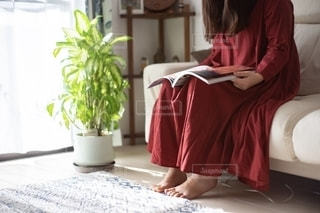 窓際のソファに座って雑誌を読む女性の写真・画像素材[2775376]
