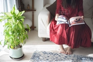 ソファに座って雑誌を読む女性の写真・画像素材[2775386]