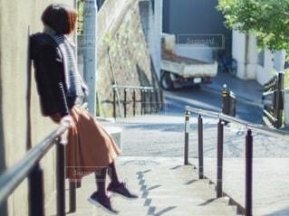 階段の手すりに腰をかけている女性の写真・画像素材[2787266]
