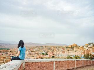 腰を下ろして遠くの街を見つめる女性の写真・画像素材[2834318]