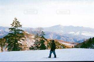 雪に覆われた山の上に立っているスノーボーダーの写真・画像素材[2851581]