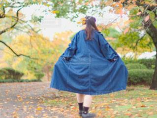 公園を歩いているデニムワンピースの女性の写真・画像素材[2862153]