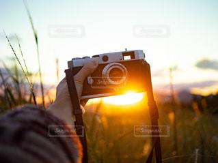 空,秋,カメラ,夕日,屋外,太陽,夕焼け,手,夕方,日没,光,ススキ,夕陽,フィルムカメラ