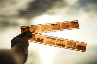 空に透かしているフィルムのネガと、人物の手の写真・画像素材[2876235]