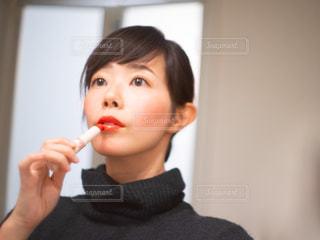 鏡の前でリップクリームを塗る女性の写真・画像素材[2883850]
