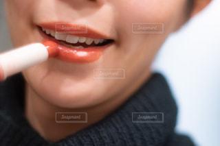 色付きリップクリームを塗る女性の唇クローズアップの写真・画像素材[2883848]