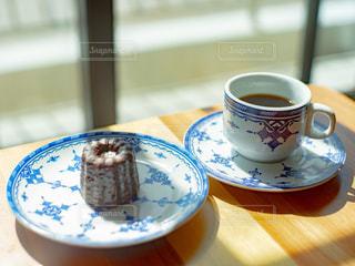 テーブルに置かれたコーヒーとカヌレとアンティーク食器の写真・画像素材[2897932]