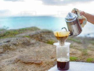 コ海が見える丘でコーヒーをドリップする人の手の写真・画像素材[2897931]