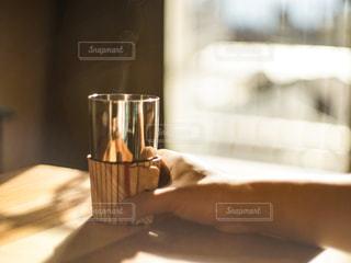 テーブルの上に置かれたコップを持つ手の写真・画像素材[2924410]