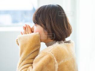 アウターで手を温めている女性の写真・画像素材[2932830]