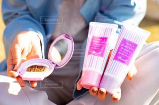 ケーキネオイルミスキンとイルミスキンを手に持つ女性の写真・画像素材[3025319]
