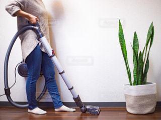 部屋で掃除機かけをしている女性の写真・画像素材[3098754]