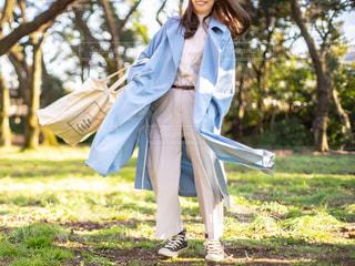 芝生の上で水色のトレンチコートとホワイトの服を着た女性の写真・画像素材[3105484]
