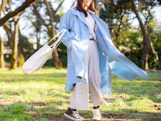 芝生の上で水色のトレンチコートとホワイトの服を着た女性の写真・画像素材[3105483]