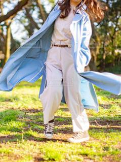 芝生の上で水色のトレンチコートとホワイトの服を着た女性の写真・画像素材[3105485]