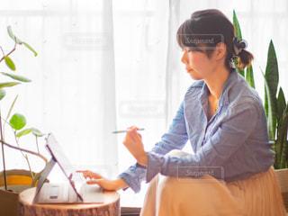 家の窓際でラップトップを操作している女性の写真・画像素材[3135719]
