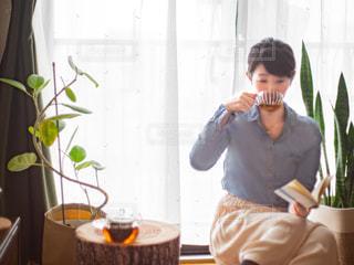窓の前に座ってお茶を飲んで本を読んでいる女性の写真・画像素材[3135720]
