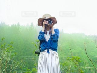 森林の中でカメラを構えている女性の写真・画像素材[3140567]
