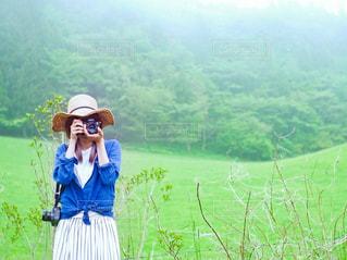 草原でカメラを構えて立っている女性の写真・画像素材[3140568]