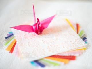カラフルな和紙の上に置いてある折り鶴の写真・画像素材[3141223]