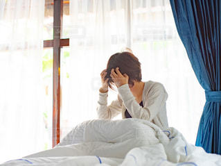 ベッドの上で髪をいじる寝起きの人の写真・画像素材[3171126]