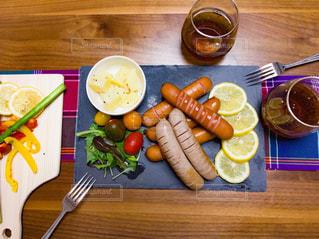 木製のテーブルの上に置かれたソーセージと野菜の写真・画像素材[3232950]