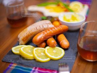 お洒落な皿の上にあるソーセージとレモンと野菜の写真・画像素材[3232957]