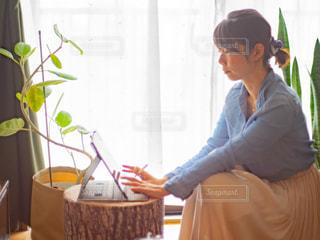 部屋の窓際でラップトップを操作する女性の写真・画像素材[3233424]