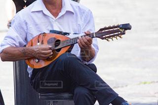 屋外でギターを演奏している男性の写真・画像素材[3233455]