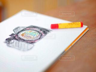 カメラの絵が描かれたスケッチブックとクレヨンの写真・画像素材[3310372]