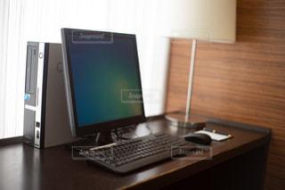 木製のデスクの上に置いてあるデスクトップコンピュータの写真・画像素材[3332439]