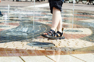 サンダルで水遊びをする女性の足の写真・画像素材[3509413]