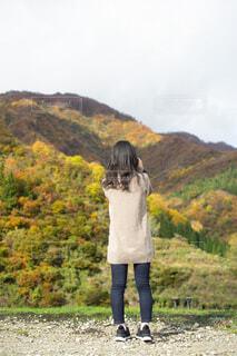 山の紅葉を眺めている女性の写真・画像素材[3702850]