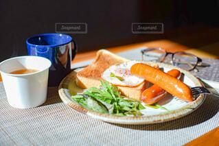 食べ物,食事,朝食,本,パン,眼鏡,テーブル,皿,食器,サラダ,カップ,朝,朝ごはん,ブレックファースト,ソーセージ,ブランチ