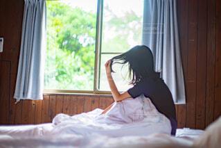 ベッドの上に座っている寝起きの女性の写真・画像素材[4060618]