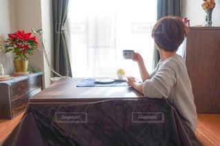 こたつでくつろぎながらコーヒーを飲む人の写真・画像素材[4143237]