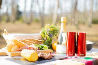 屋外のテーブルに置かれたシャンパンフルートとキャンプ飯の写真・画像素材[4171771]