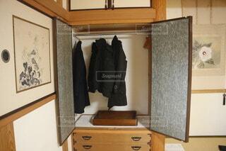 和室のクローゼットにかけられた衣類とと収納ケースの写真・画像素材[4213862]