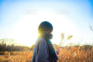 ドライフラワーを持って夕日を見ているマフラーとコートを着た女性の写真・画像素材[4286812]