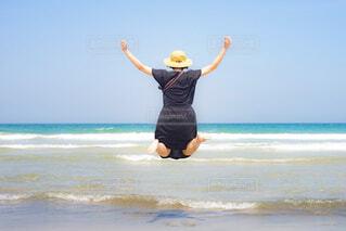 砂浜でジャンプをする女性とビーチの写真・画像素材[4306419]
