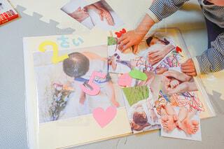 アルバムに写真を貼り付けている子どもの写真・画像素材[4318071]
