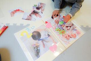 アルバムに写真とデコレーションを貼っている子供の手の写真・画像素材[4318069]