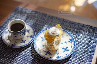 テーブルの上に置かれたコーヒーとケーキとアンティークの食器の写真・画像素材[4324491]