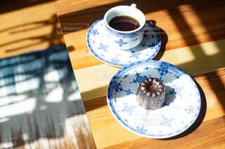 テーブルの上に置かれたコーヒーとカヌレの写真・画像素材[4324492]