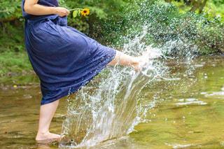 川で水を蹴って遊んでいる女性の写真・画像素材[4373020]