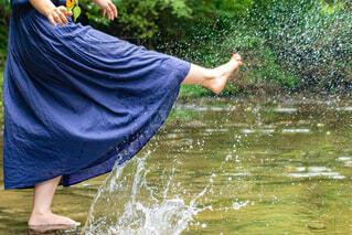 川で水を蹴って遊んでいる女性の足の写真・画像素材[4373019]