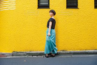 屋外で立っている青いロングスカートの女性の写真・画像素材[4559506]