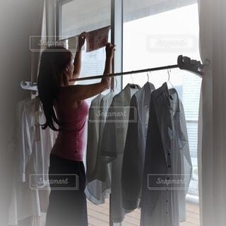 室内で洗濯物を干す人の写真・画像素材[4625552]