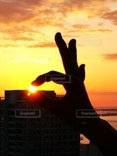 夕日を指で摘んで遊ぶの写真・画像素材[4660859]